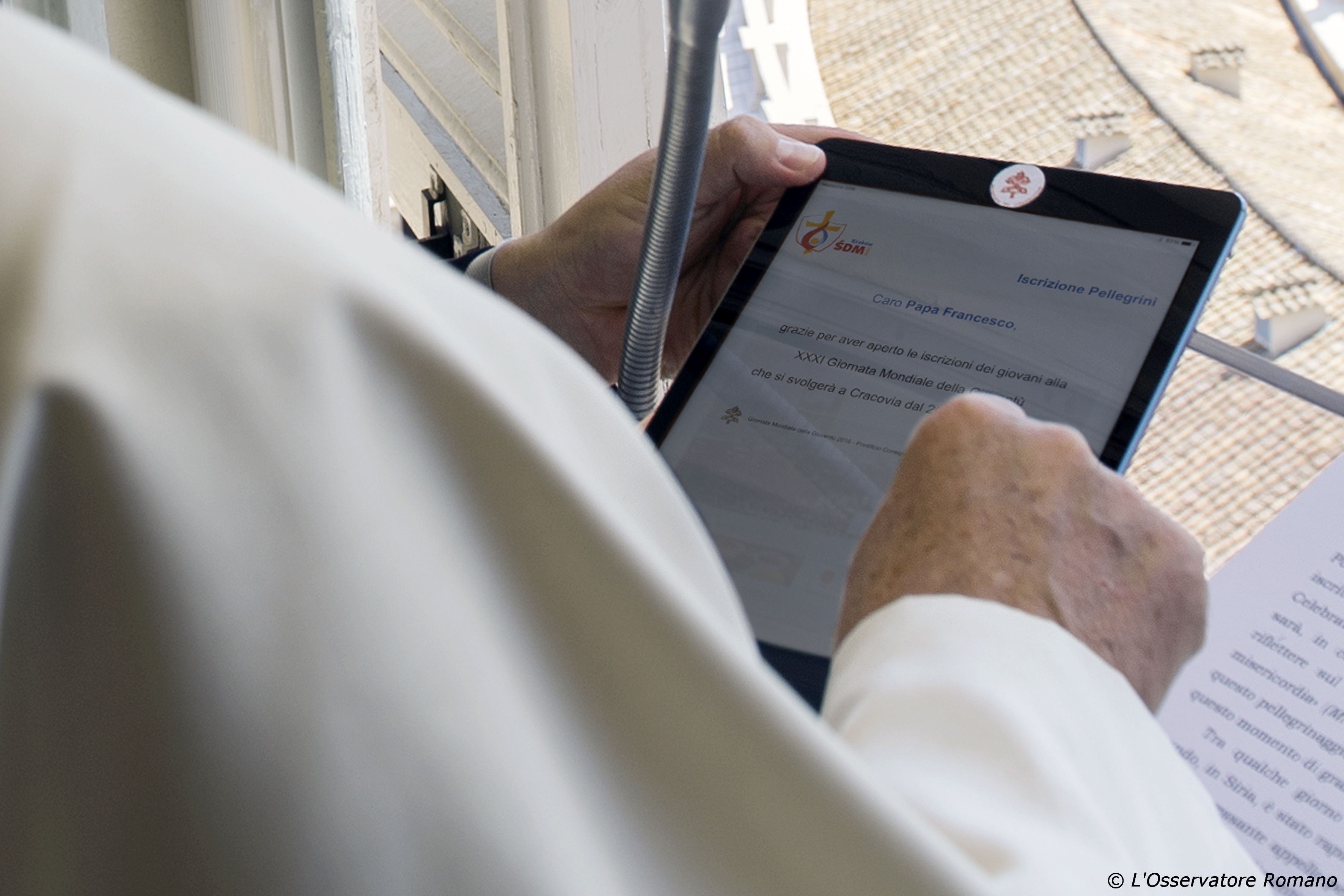 Pope Francis registers himself through a tablet as a pilgrim to the 2016 World Youth Day in Poland