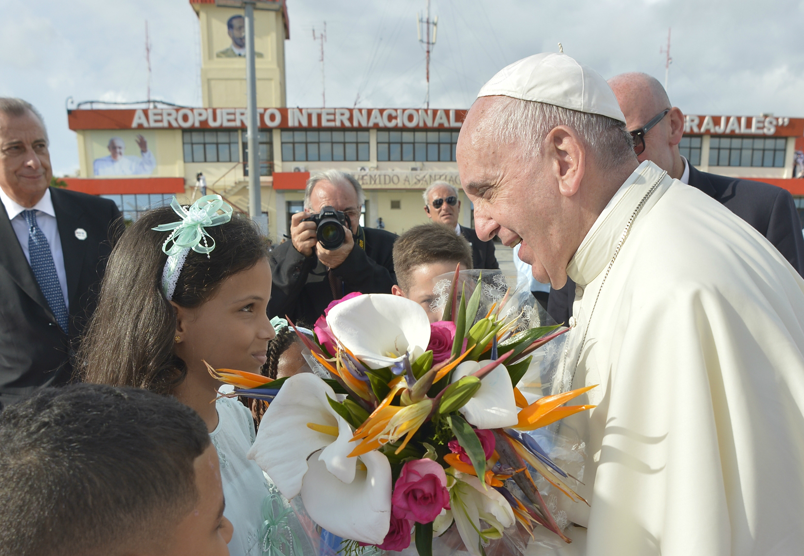 Pope Francis receives flowers at his arrival at the International Airport of Santiago de Cuba