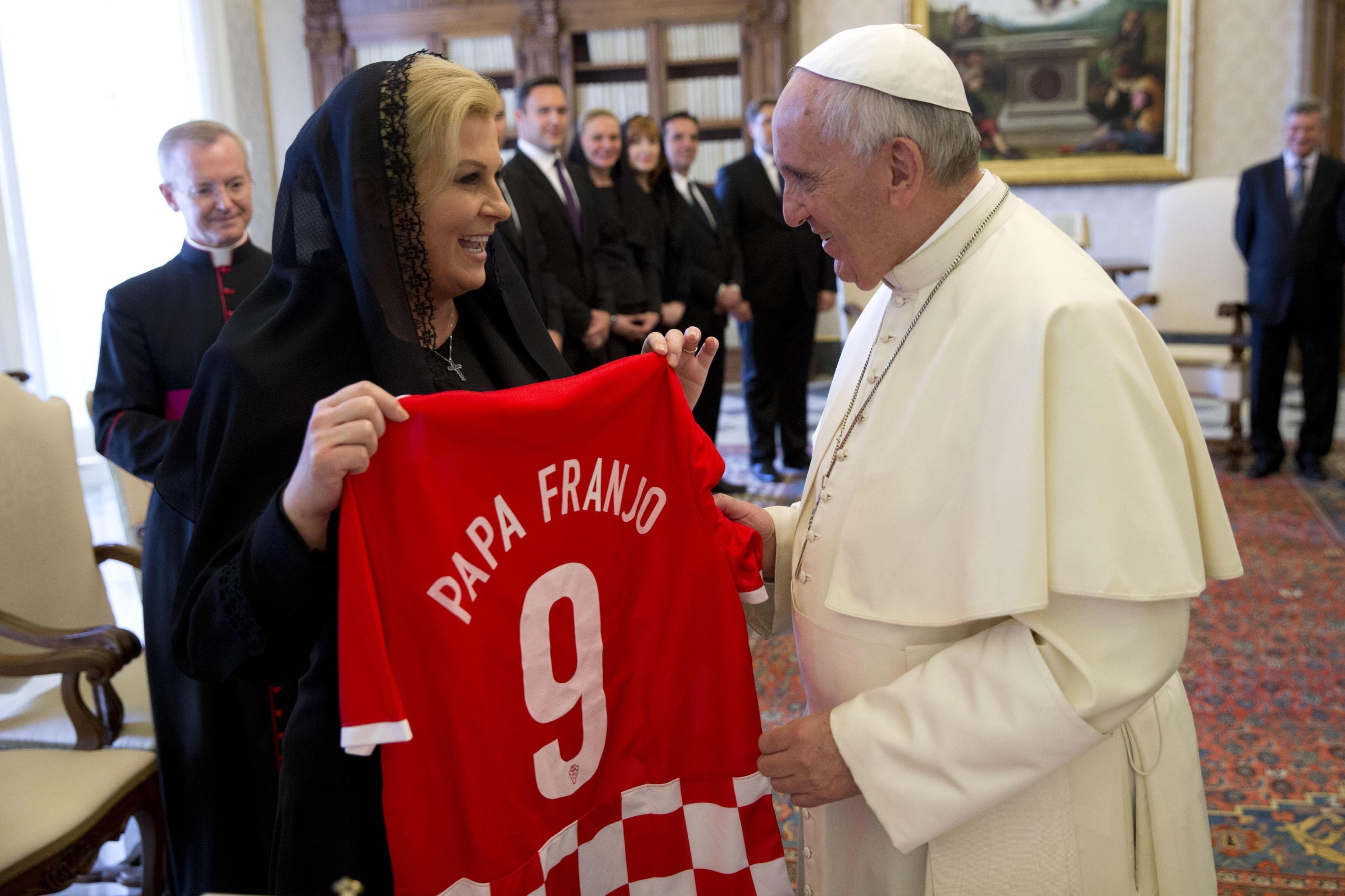 Pope Francis receives a national soccer team jersey bearing his name from Croatia's President Kolinda Grabar Kitarovic