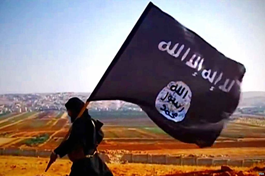 A member of the organization with the flag of the Islamic State