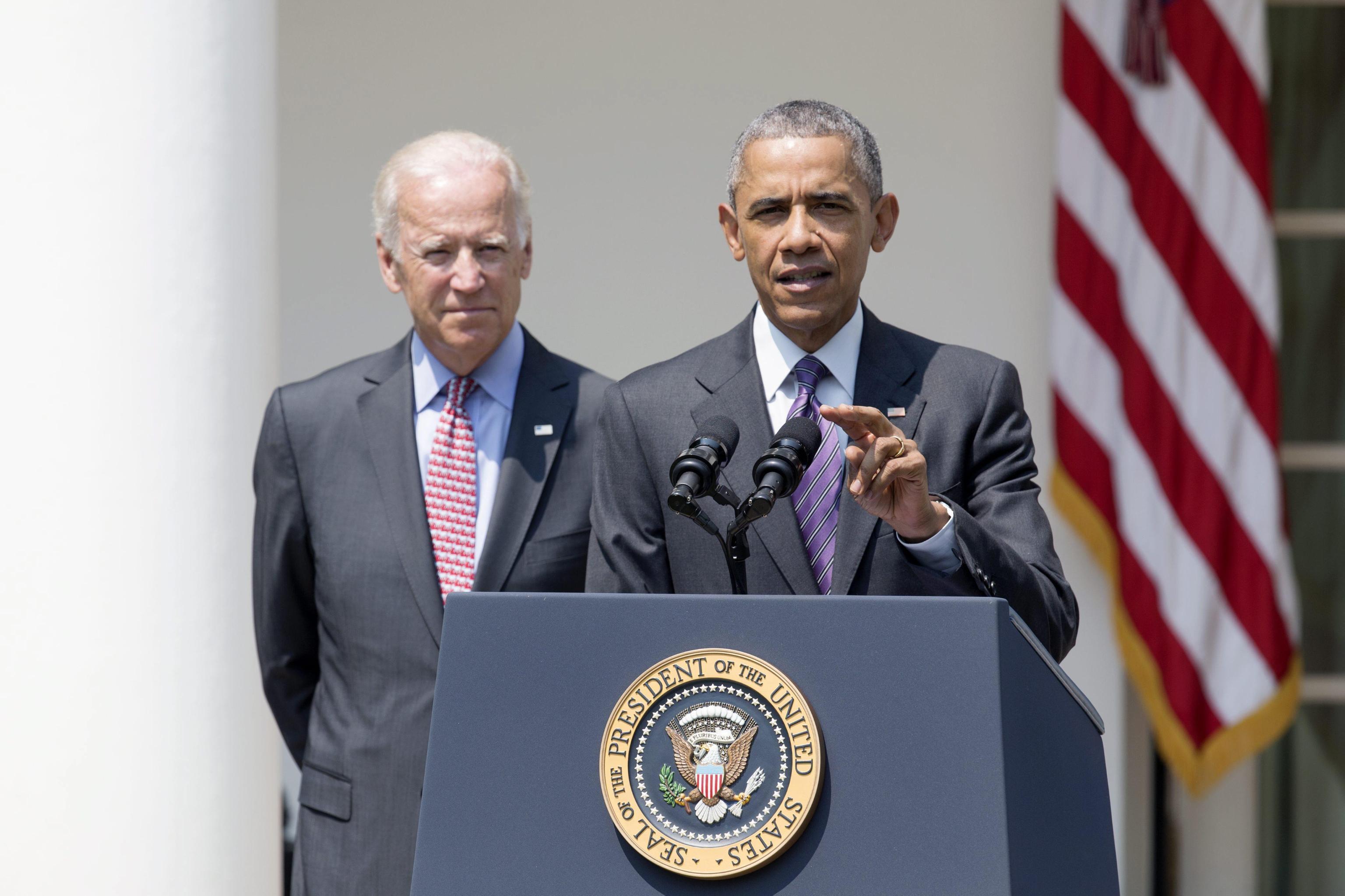 US President Barack Obama (R) makes a statement on Cuba