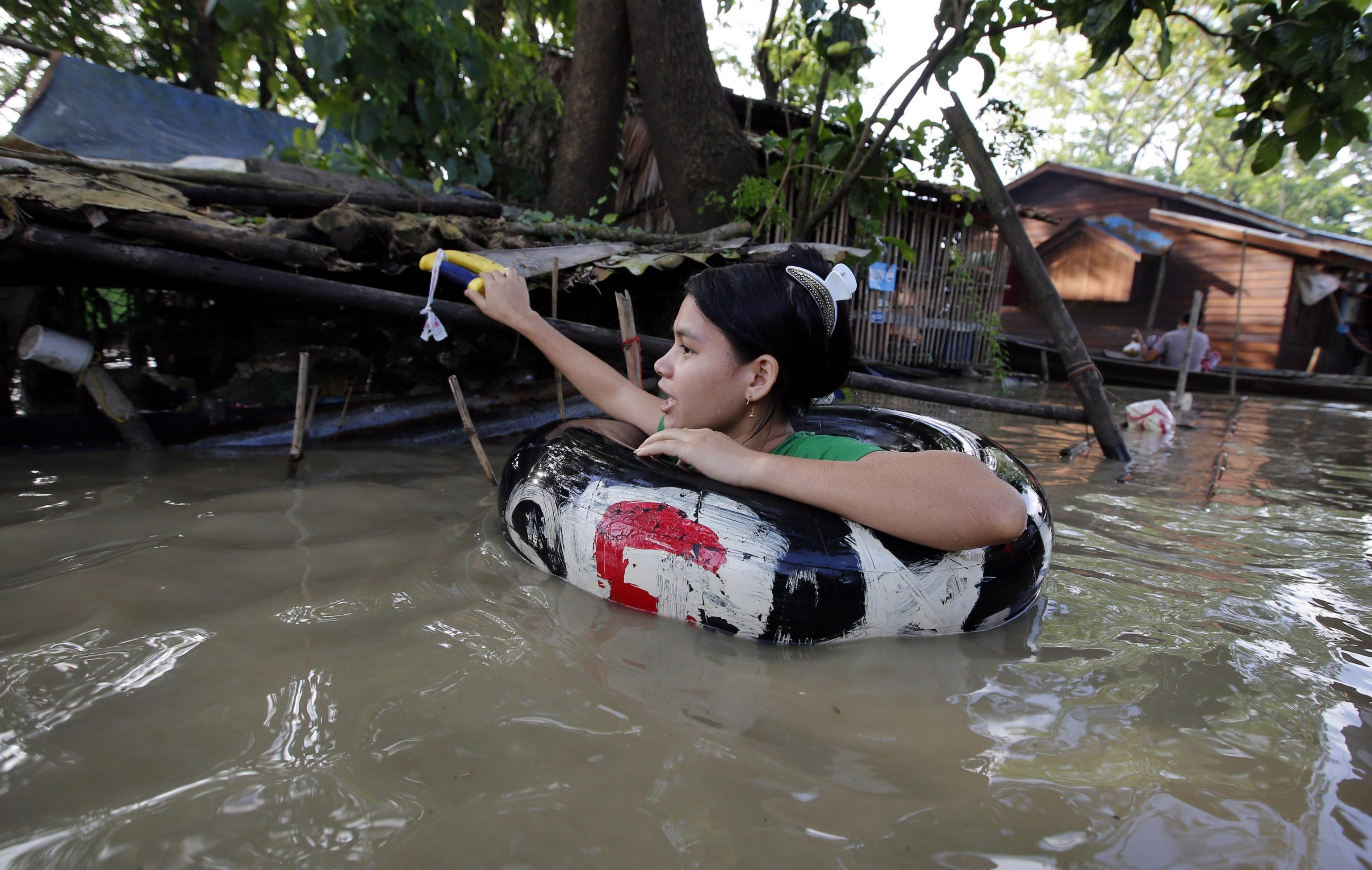 A Myanmar girl uses an inflatable rubber tube to wade through a flooded street in Nyaung Don township of Ayeyarwaddy Region