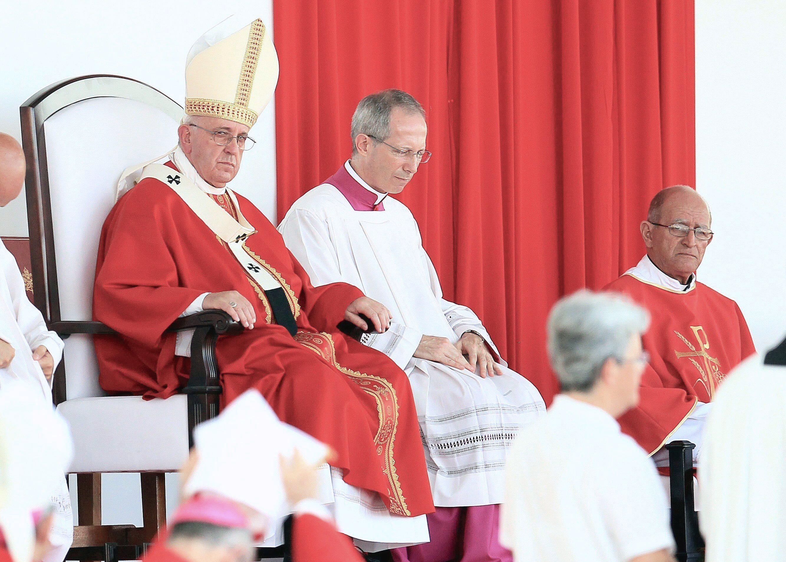 Pope Francis (L) looks on during a mass at Revolution Square in the city of Holguin