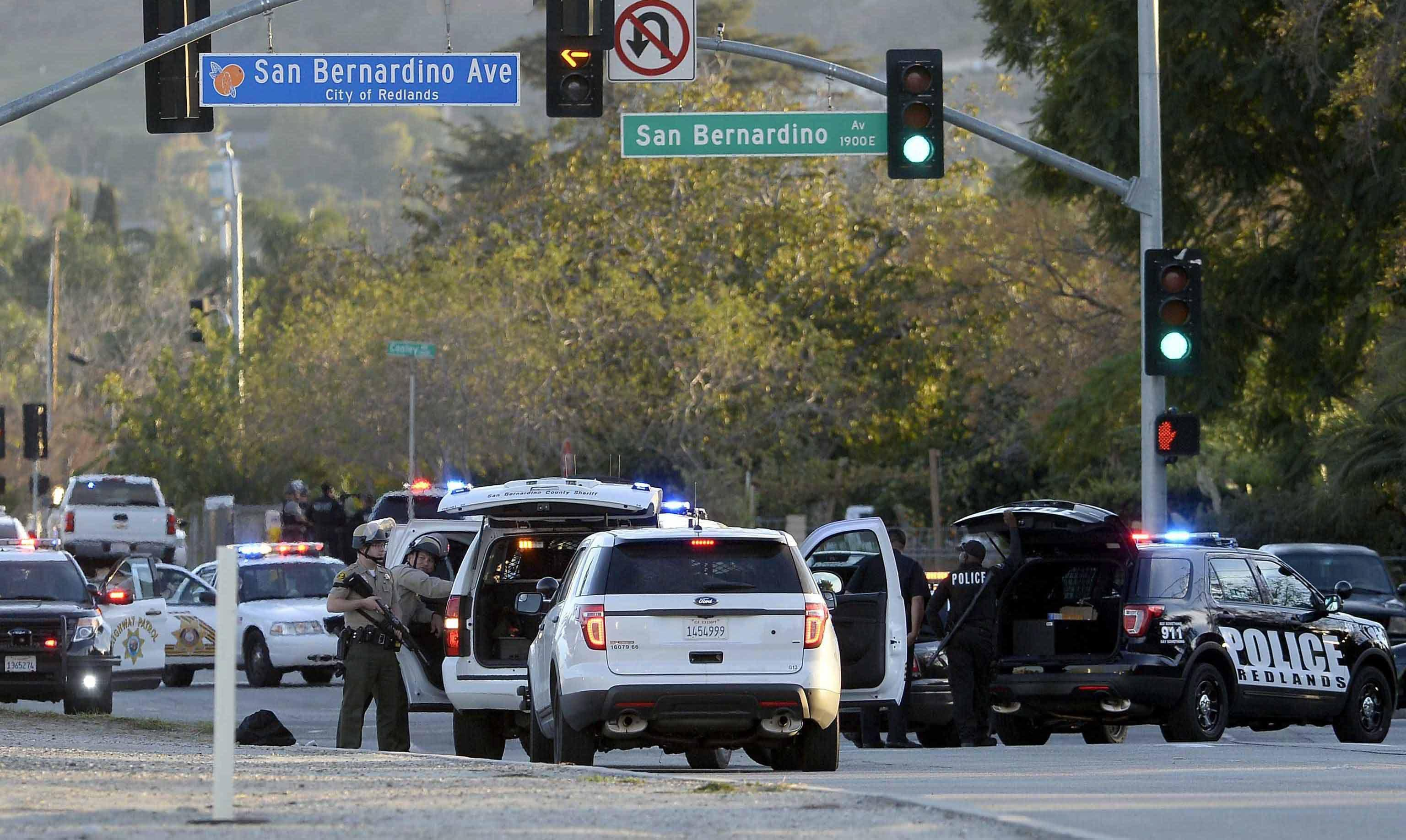 Law enforcement officers deploy near the scene where suspects in the shooting at the Inland Regional Center were reportedly apprehended in San Bernardino