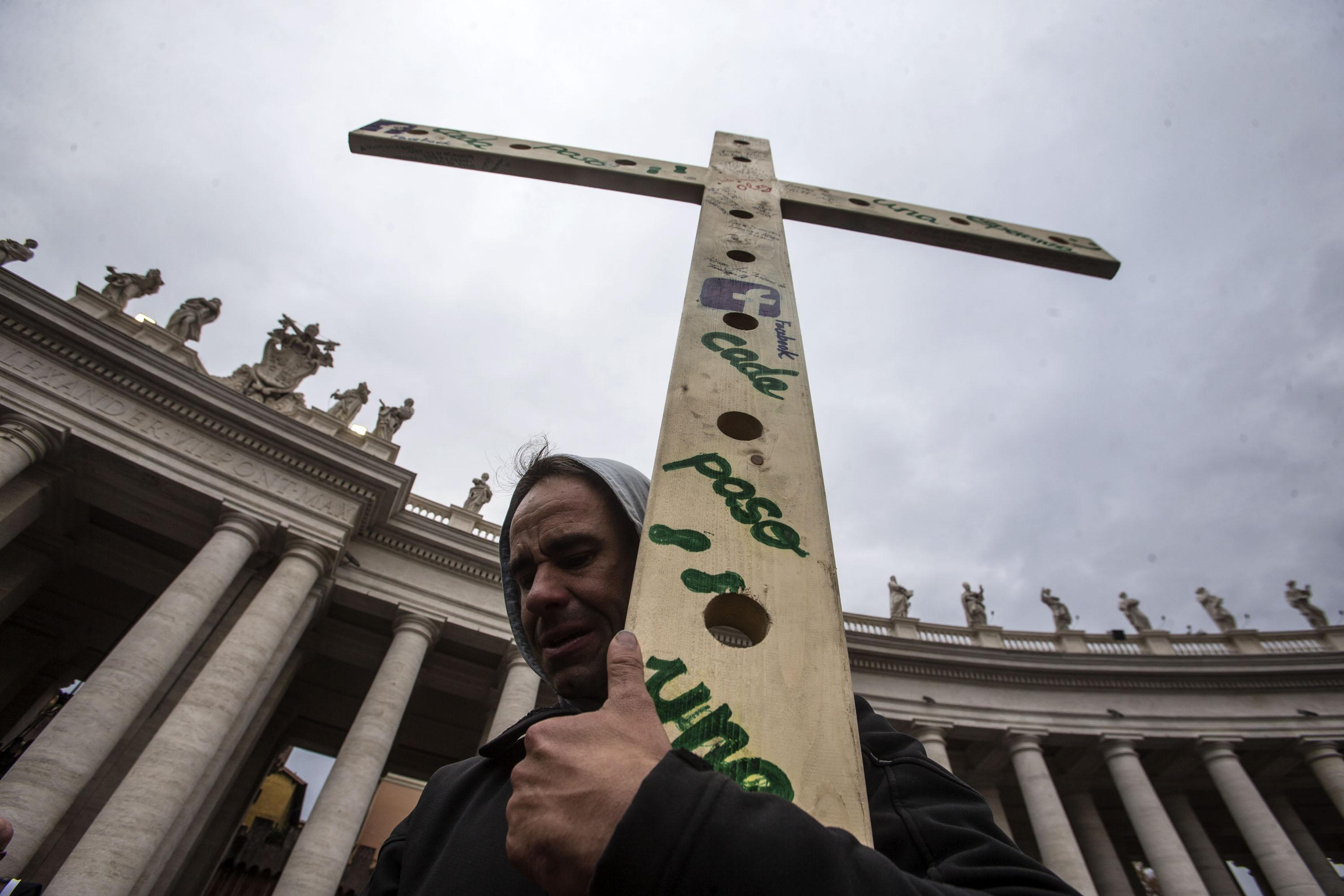 A faithful supports a cross during the mass celebrated by Pope Francis prior to the opening of the Holy Door of Saint Peter's Basilica