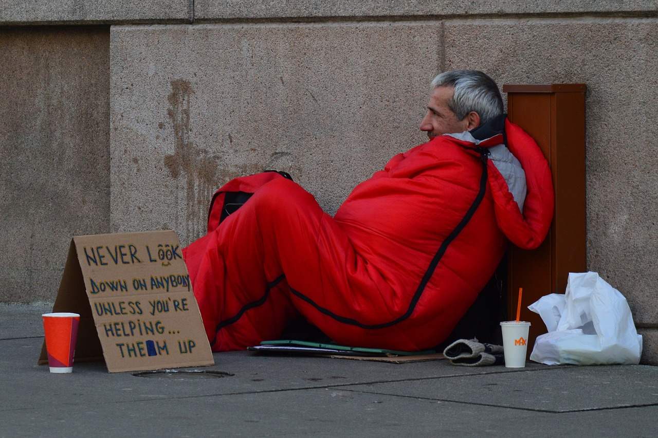 """Homeless person with a sign """"Never look down on anybody"""