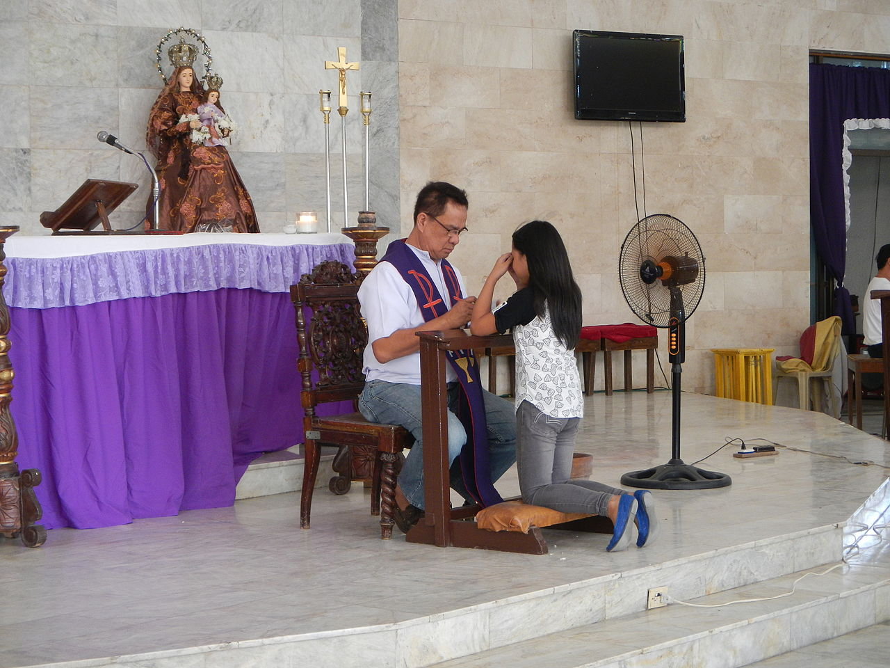 A priest hearing confession in a parish in the Philippines