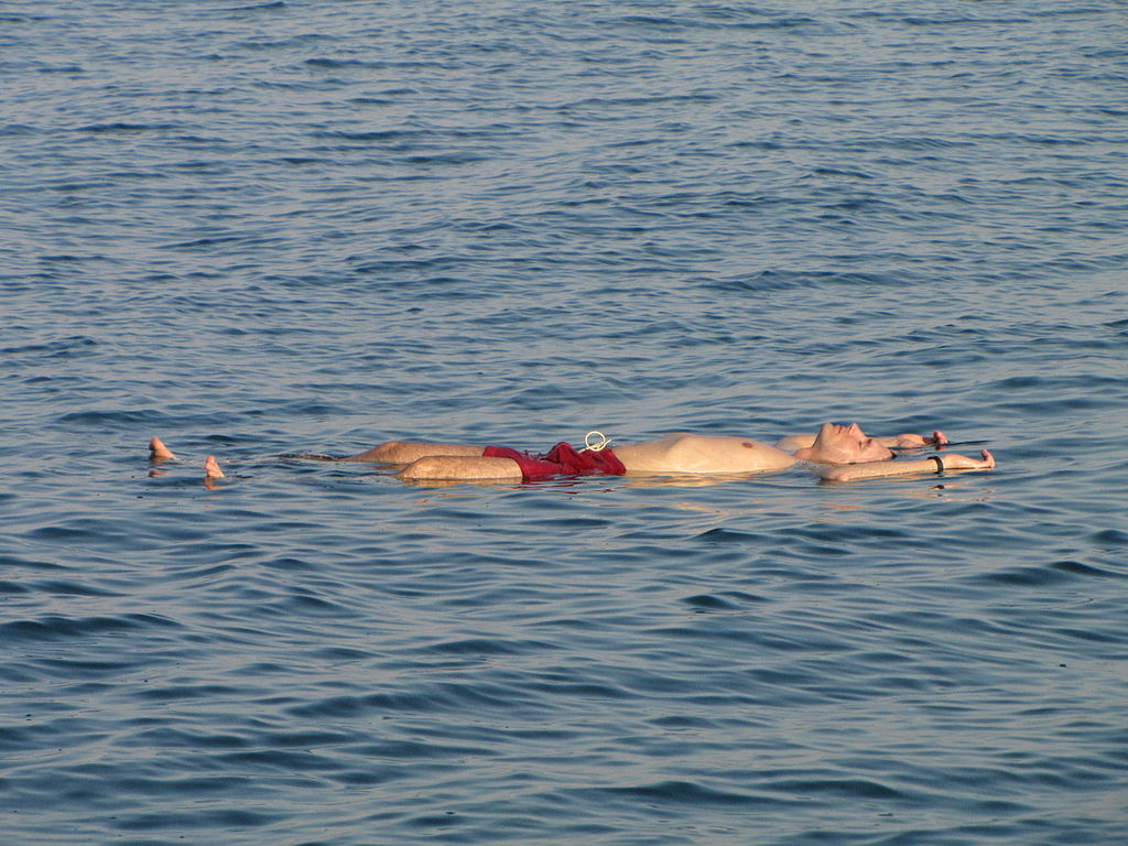 """A man """"swimming"""" or floating in the extremely saline waters of the Dead Sea"""