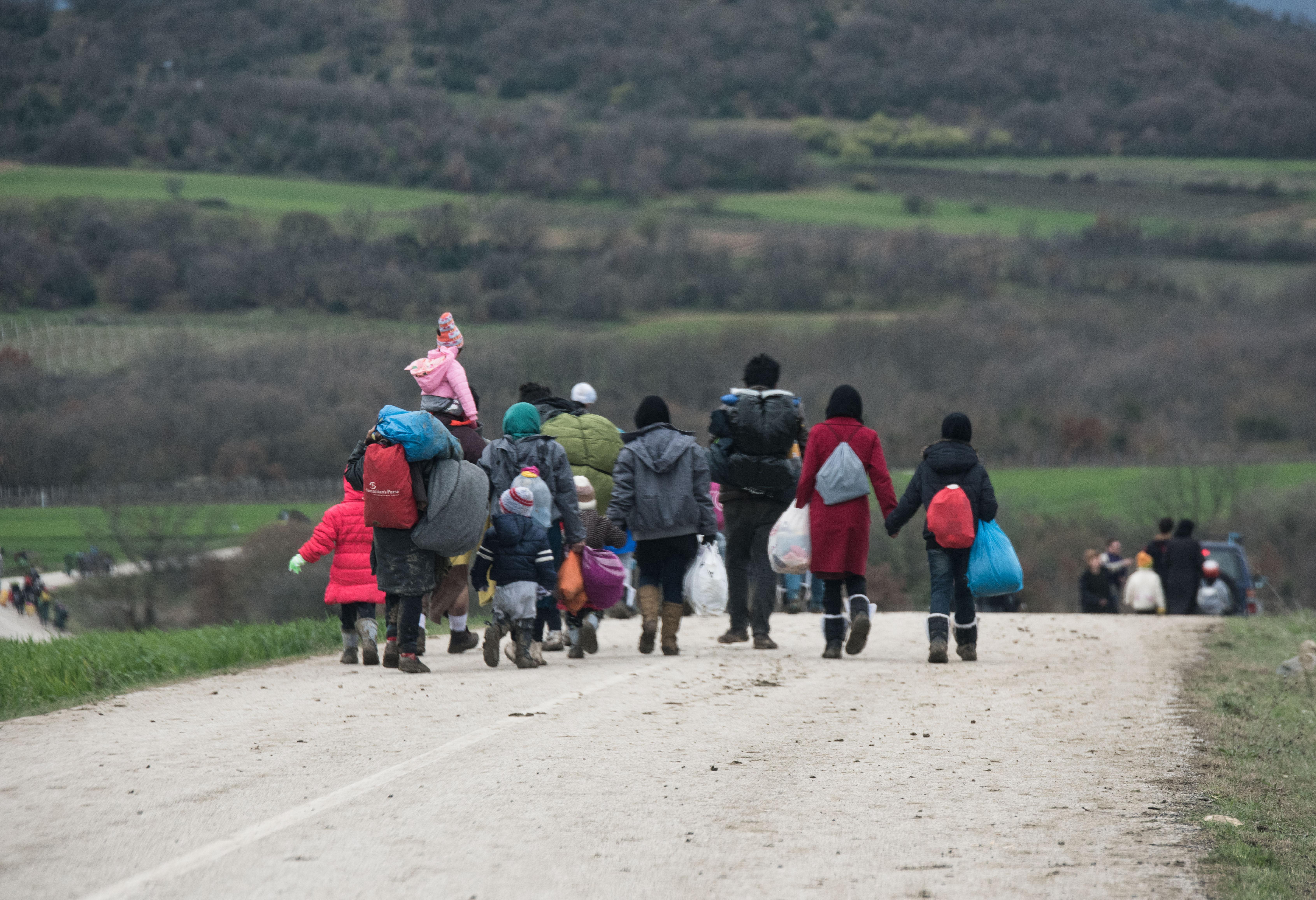 immigrants cross the border between Greece and Macedonia